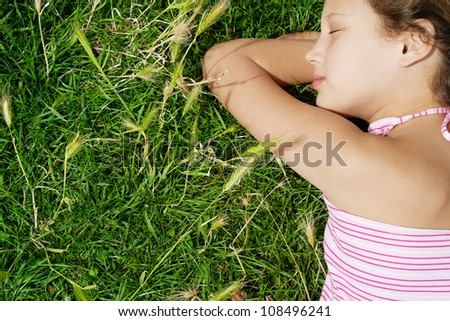 Close up rear view of a young girl sleeping on green grass in the park. - stock photo