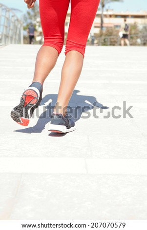 Close up rear view of a young woman legs jogging and doing exercise during a sunny day, wearing red sport wear and running on a flat pavement in a city, outdoors. Healthy sport lifestyle.