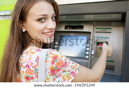 Close up rear view of an attractive young woman using a cash point machine to withdraw money, inserting her credit card, turning and smiling during a sunny day outdoors. Finance and lifestyle. - stock photo