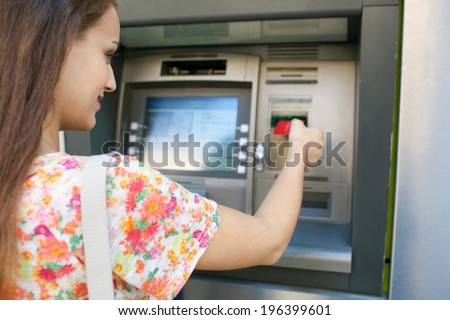 Close up rear view of an attractive young woman using a cash point machine to withdraw money, inserting her credit card and smiling during a sunny day outdoors. Finance and lifestyle. - stock photo