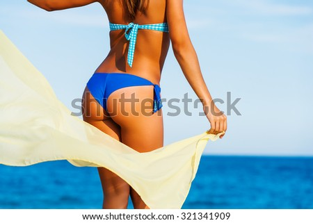 Close up rear view of Attractive female suntanned body on beach. Young woman in blue bikini playing with yellow scarf in wind.