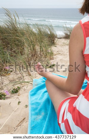 Close up rear view of slim woman meditating in a yoga position - stock photo