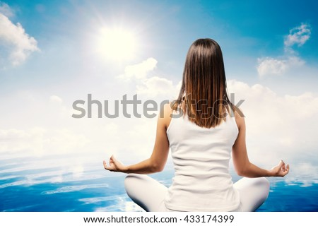Close up rear view of young woman meditating at water side. Girl in white sitting looking at sun and clouds.