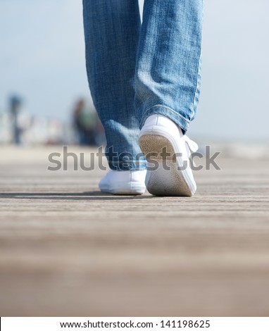 Close up rear view portrait of a woman walking in comfortable white shoes outdoors - stock photo