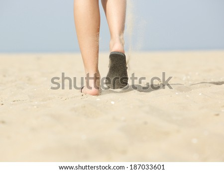 Close up rear view woman walking on sand at beach in slippers - stock photo