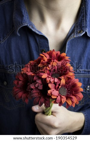 Close up red flowers being held by man - stock photo
