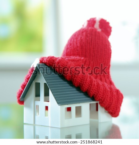Close up Red Knitted bobble hat on Top of Cute Little House Placed on the Table. - stock photo
