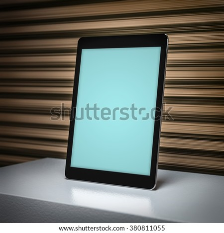 Close-up render of a black tablet pc device on a bookshelf. Clipping path for display included.