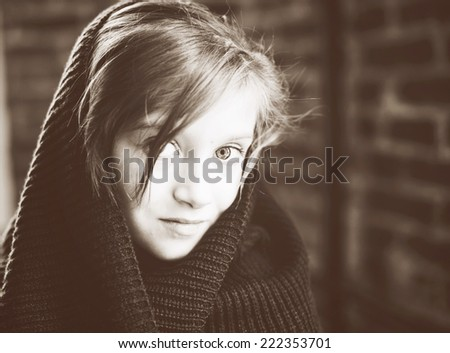 Close-up  retro portrait of brunette child girl, in knitted snood sepia tone added - stock photo