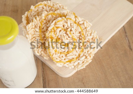 Close up rice crackers with Bottle glass of Milk on a wooden table. Rice crackers with Bottle glass of Milk. - stock photo