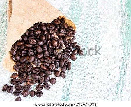 Close up roasted coffee beans in paper bags on wooden background