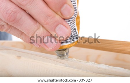Close Up Rough Hand Squeezing Wood Glue on Cabinet. - stock photo
