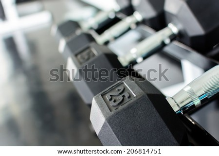 Close up rows of dumbbells on a rack in a gym - stock photo