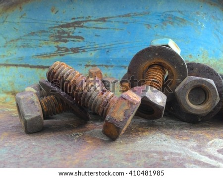 Close-up, rusted screws large overlap pile on the floor, steel blue backdrop. - stock photo