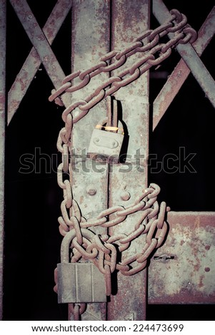 Close -up rusty chain and master key locked on grunge iron gate - stock photo