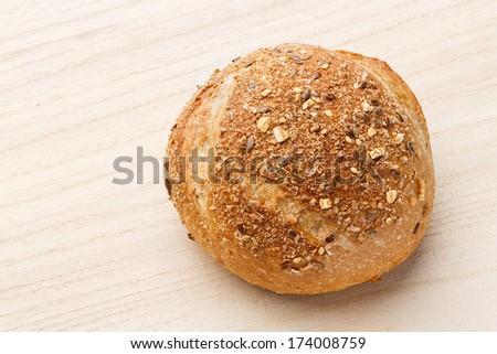 Close up rye multigrain bread on wood chopping board - deep focus image - stock photo