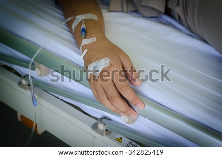 Close up saline IV drip for patient and Infusion pump in hospital - stock photo