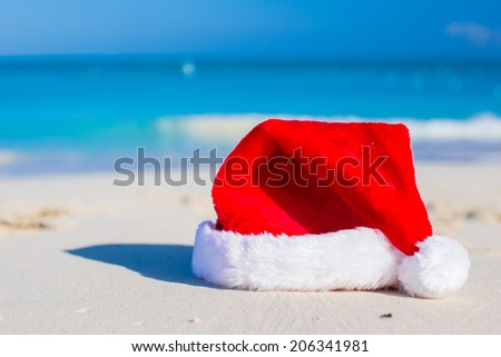 Close up Santa hat on a white sandy beach - stock photo