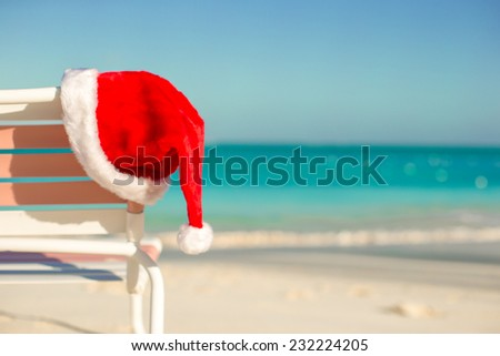 Close up Santa hat on chair longue at tropical beach - stock photo
