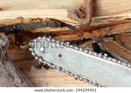 close-up saw on the background of chopped firewood in the sunlight  - stock photo