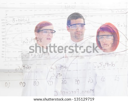 close-up seen through a transparent board ot three scientists in a chemistry lab  pointing and analyzing formulas on it - stock photo