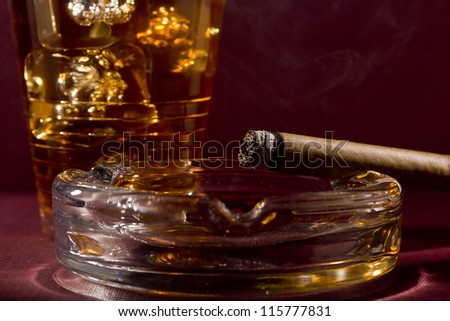 Close-up selective focus of a burning cigar with a glass of whiskey in the background. - stock photo