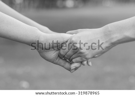 close up/selective focus of couple women hands holding/touching together for helping:helping hand grasp concept:family and friends concept.grey color tone color.happy family.kindness concept - stock photo