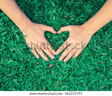 close up/selective focus on man hand make heart shape on green grass background in vintage effect:soft focus love symbol on garden park outdoor concept:take care of  environment/ecology globe image - stock photo