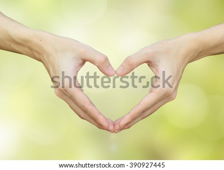 close up/selective focus on man hands make heart over blurred bright blue color with bokeh light background:shallow man hand making heart-shape for showing healthy life:happy good healthcare concept. - stock photo