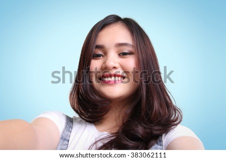 Close-up self-shot portrait of cute Asian teenage girl smiling over blue background - stock photo