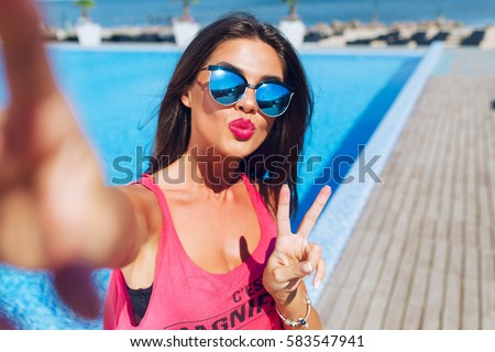 Close-up selfie-portrait of attractive brunette girl with long hair standing near pool. She wears pink T-shirt, sunglasses. She shows a kiss to the camera and makes cool look.