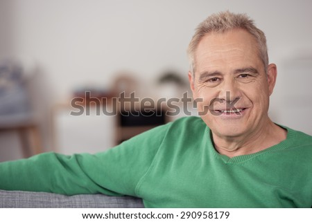 Close up Senior Blond Man in Green Shirt, Sitting on Sofa at Home and Smiling at the Camera - stock photo
