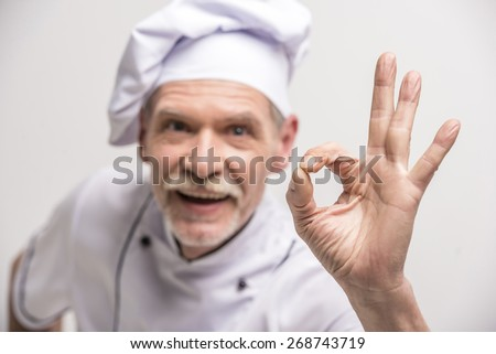 Close-up. Senior male chief cook in uniform gesturing okay sign on grey background. - stock photo