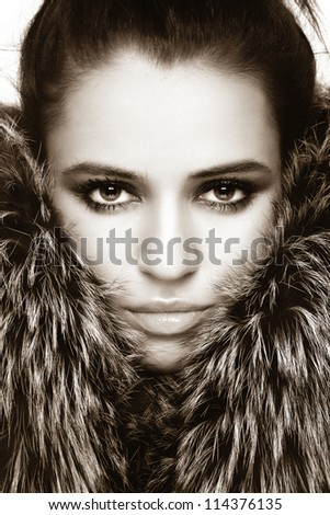Close-up sepia portrait of young beautiful woman with stylish make-up and fur around her face - stock photo