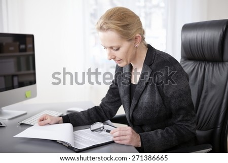 Close up Serious Blond Businesswoman at her Office Scanning Business Documents with Magnifying Glass. - stock photo
