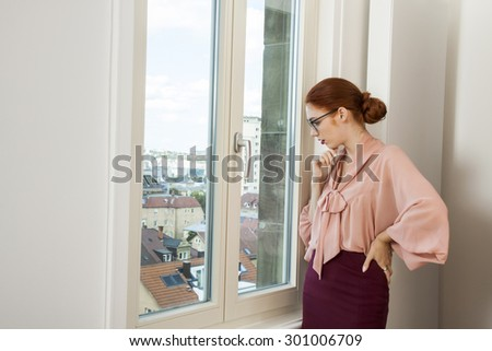 Close up Serious Pretty Office Woman in Stylish Business Attire Looking Outside Through Glass Window - stock photo