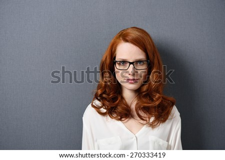 Close up Serious Pretty Young Woman, in White Shirt and Eyeglasses, Staring at the Camera on a Gray Background with Copy Space. - stock photo