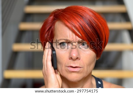 Close up Serious Redhead Adult Woman Calling Someone on her Mobile Phone While looking Into the Distance. - stock photo