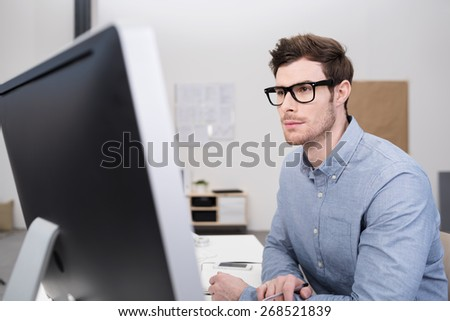 Close up Serious Young Businessman with Eyeglasses Sitting at his Worktable inside the Office and Facing a Computer Monitor - stock photo