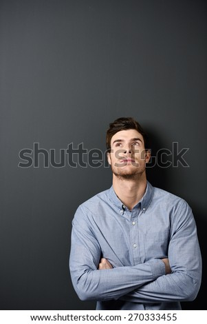 Close up Serious Young Handsome Man in Long Sleeves Shirt Leaning on Gray Wall with Arms Crossed and Looking Up, Emphasizing Texts Space at the Left Side. - stock photo