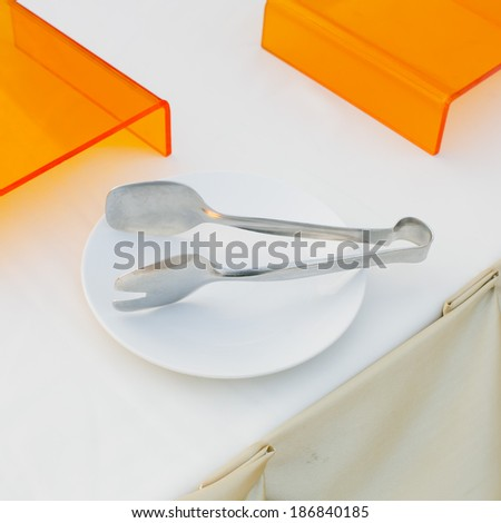 close up serving kitchen tongs - stock photo