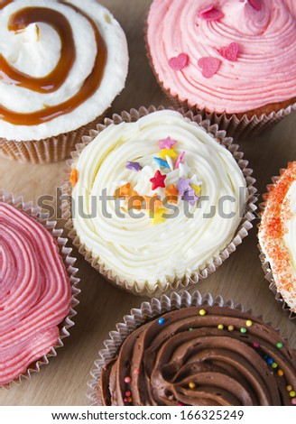 Close up set of colorful cupcakes on wooden background, brown table. Chocolate Cupcake, strawberry pink, bright white vanilla. Cafe, restaurant, sweets, cakes. - stock photo