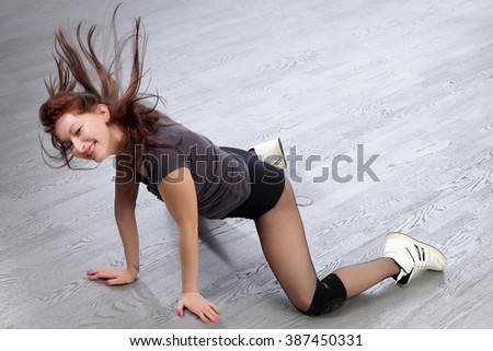 close-up sexy redhead girl showing sports buttocks on a background of gray flooring studio