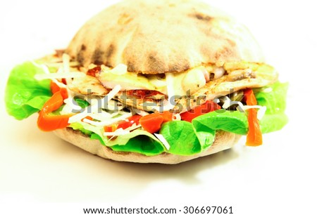 Close-up (shallow dept) of a sandwich filled with meat, lettuce, cheese and peppers. Tasty! - stock photo