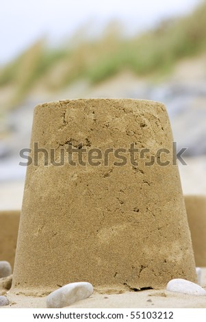 Close up shallow depth of field photo of a sandcastle - stock photo