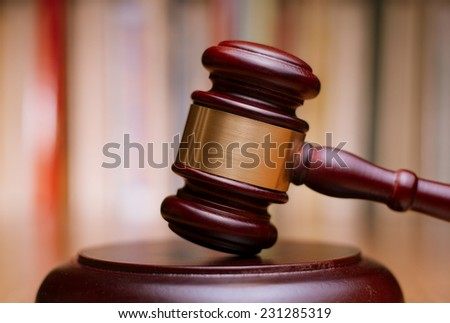 Close up Shiny Wooden Law Gavel in Dark Brown Color, on Top of Wooden Table at the Office.
