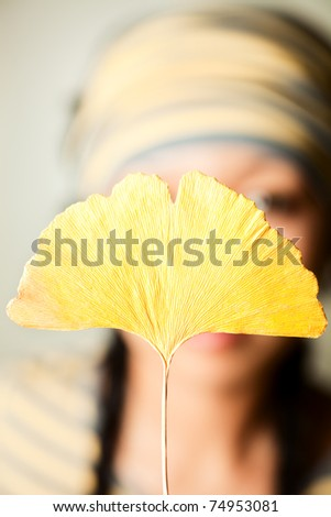 Close up shoot girl holding yellow leaf.