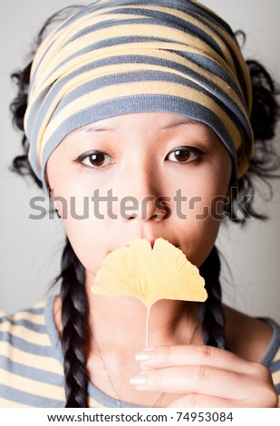 Close up shoot girl holding yellow leaf. - stock photo