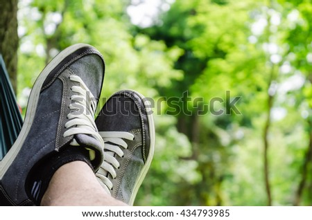 Close up shoot of a pair of sneakers in hammock in park.