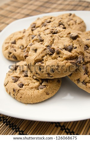 close up shoot of chocolate cookies on a white dish over a mat - stock photo